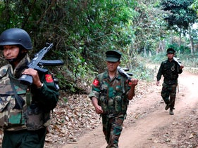 Kachin Independence Army fighters walk in a jungle path from Mu Du front line to Hpalap outpost in an area controlled by the Kachin rebels in northern Kachin state, Myanmar, March 17, 2018.