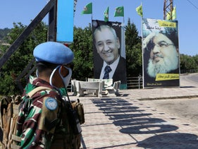 A United Nations peacekeeper stands near a poster depicting Lebanon's Hezbollah leader Hassan Nasrallah near the Lebanese-Israeli border, August 7, 2020.