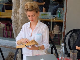 A woman reading a book at a cafe in Jaffa, Israel, September 2020.