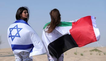 Israeli model May Tager, left, holds Israel's blue-and-white flag bearing the Star of David while next to her Anastasia Bandarenka, a Dubai-based model originally from Russia, waves the Emirati flag, during a photo shoot modeling pajamas by the Israeli fashion brand Fix, in Dubai, United Arab Emirates, Sunday, Sept. 8, 2020