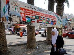 A banner showing Arab countries's flags is seen as a woman walks during a protest against normalizing ties with Israel, in Nablus, West Bank, September 9, 2020.