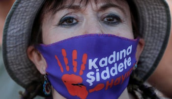 """A demonstrator wearing a face mask with a sign reading: """"No to violence against women"""", at a protest against femicide and domestic violence in Istanbul, Turkey, August 5, 2020."""