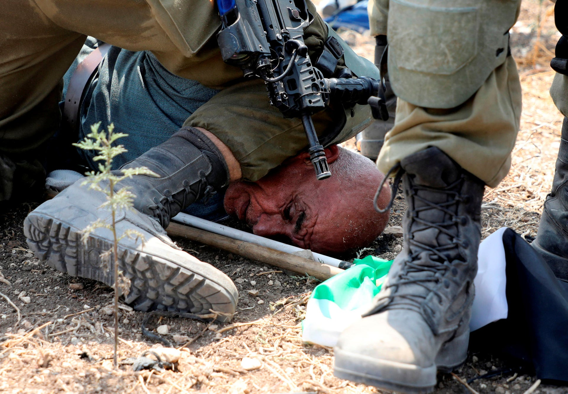 An IDF soldier pins Khairi Hanoun to the ground with his knee on his neck, in Shufa.