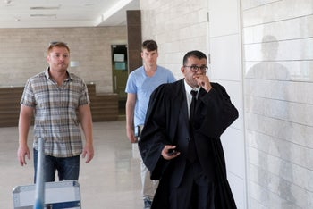 Prosecutor Nissim Merom (R) accompanied by security guards at the Lod District Court, August 29, 2017.