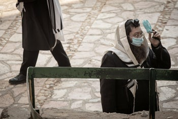 A man in Bnei Brak does the morning prayer while socially distancing and wearing a mask, September 9, 2020.