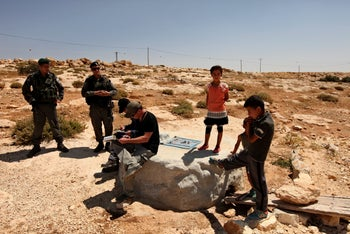 Civil Administration inspectors issue orders to Palestinians to halt works in the West Bank village of Susya, June 27, 2013