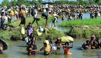 Rohingya refugees walk through a shallow canal after crossing the Naf River in Palongkhali, as they flee violence in Myanmar to reach Bangladesh, October 16, 2017.