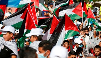 Palestinians wave national flags as they protest against the United Arab Emirates' decision to normalize ties with Israel, in the village of Turmus Aya in the West Bank, August 19, 2020.