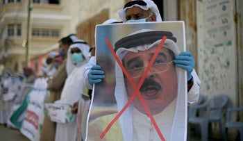 A Palestinian man holds a crossed out poster of Bahrain's King Hamad bin Isa Al Khalifa during a protest against Bahrain's move to normalize relations with Israel, Gaza, September 12, 2020.