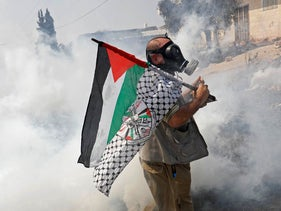 A demonstrator holds a Palestinian flag as Israeli forces fire tear gas during a protest against Gulf states normalizing ties with Israel, Kafr Qaddum, West Bank, September 11, 2020.
