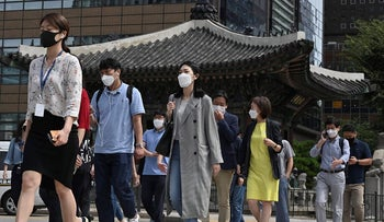 People wearing face masks cross a road in Seoul on September 11, 2020. - South Korea largely overcame an early COVID-19 coronavirus outbreak with extensive tracing and testing, but is now battling several outbreaks