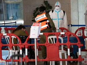 File photo: A person wearing a protective suit is seen talking to a soldier from the IDF's Home Front Command at Ben-Gurion International Airport during a lockdown, April 19, 2020.