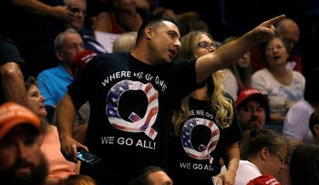 Supporters wearing shirts with the QAnon logo, chat before U.S. President Donald Trump takes the stage during his Make America Great Again rally in Pennsylvania, August 2, 2018.