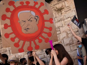 A protester holds a sign depicting Prime Minister Benjamin Netanyahu as the coronavirus during a protest against him outside his official residence in Jerusalem, July 31, 2020.