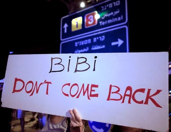 An Israeli protester holds a placard against Israeli Prime Minister Benjamin Netanyahu before his flight to the U.S. to sign an accord with the UAE and Barhain, Israel, September 13, 2020.