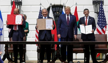 Representatives display their copies of signed agreements while U.S. President Donald Trump looks on at the signing ceremony in Washington, U.S., September 15, 2020.