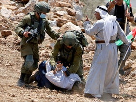 Israeli soldiers detain a Palestinian demonstrator during a protest against settlements near Tulkarm in the West Bank on August 20, 2020.
