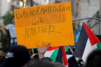 A Palestinian demonstrator holds a sign during a protest against the United Arab Emirates and Bahrain's deal with Israel to normalize relations, in Ramallah, September 15, 2020.
