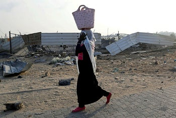 A Palestinian woman passes the scene of an Israeli air strike at Hamas site in the northern Gaza Strip September 16, 2020.