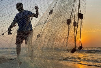 A Palestinian fisherman repairs his net at a beach during a lockdown amid the coronavirus disease (COVID-19) outbreak, in the northern Gaza Strip September 10, 2020.