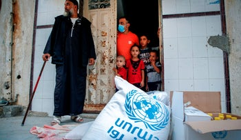 Members of a Palestinian family stand through the door of their home as they receive food aid provided by UNRWA in Gaza City on September 15, 2020