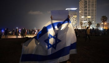 Protesters waving the Israeli flag during a demonstration against Prime Minister Benjamin Netanyahu in Tel Aviv, July 2020.