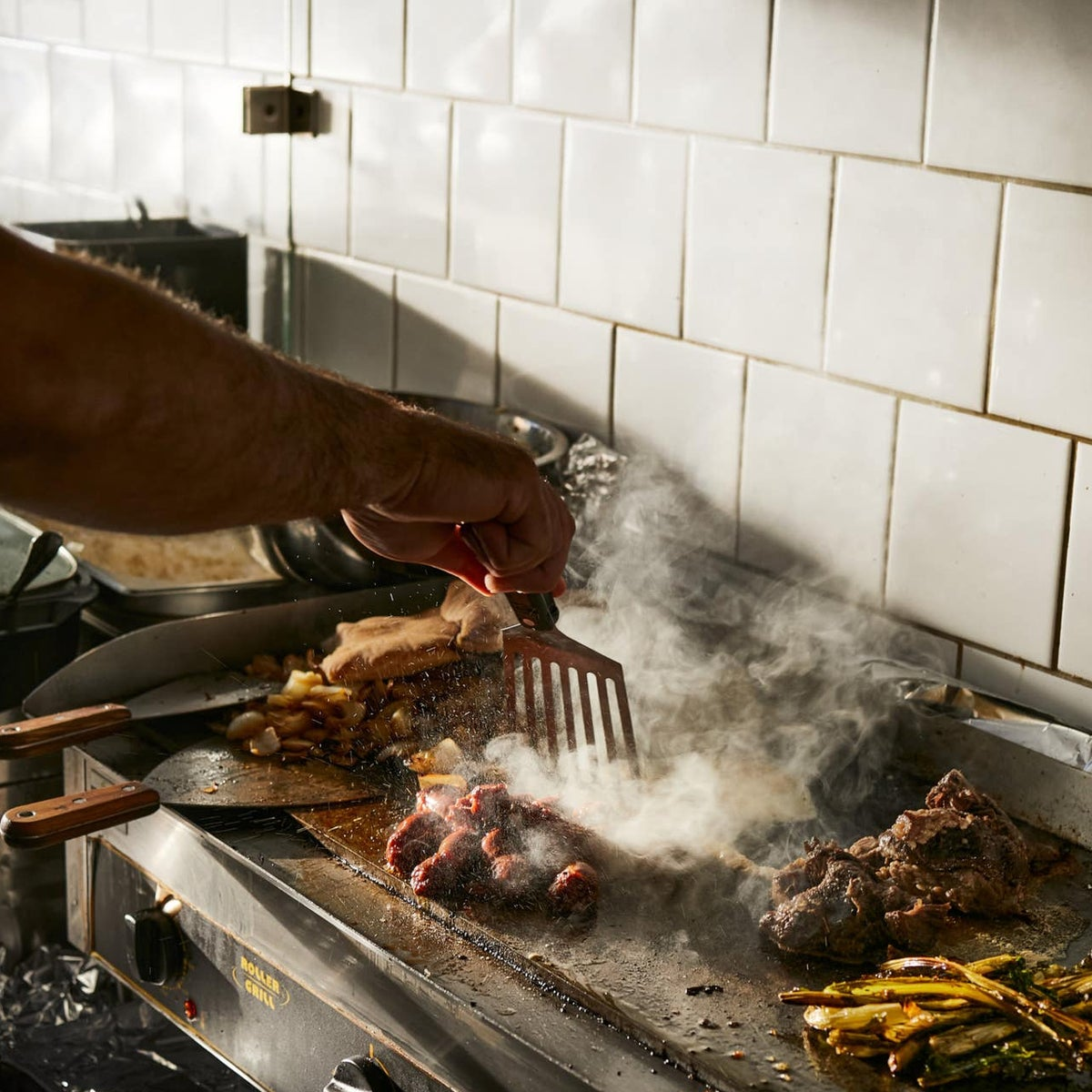 In for the grill: Preparing food for hungrey diners at Zalmanico, Jaffa.