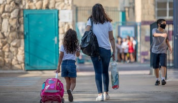An adult accompanies a schoolchild in Jerusalem on the first day of school, September 1, 2020.