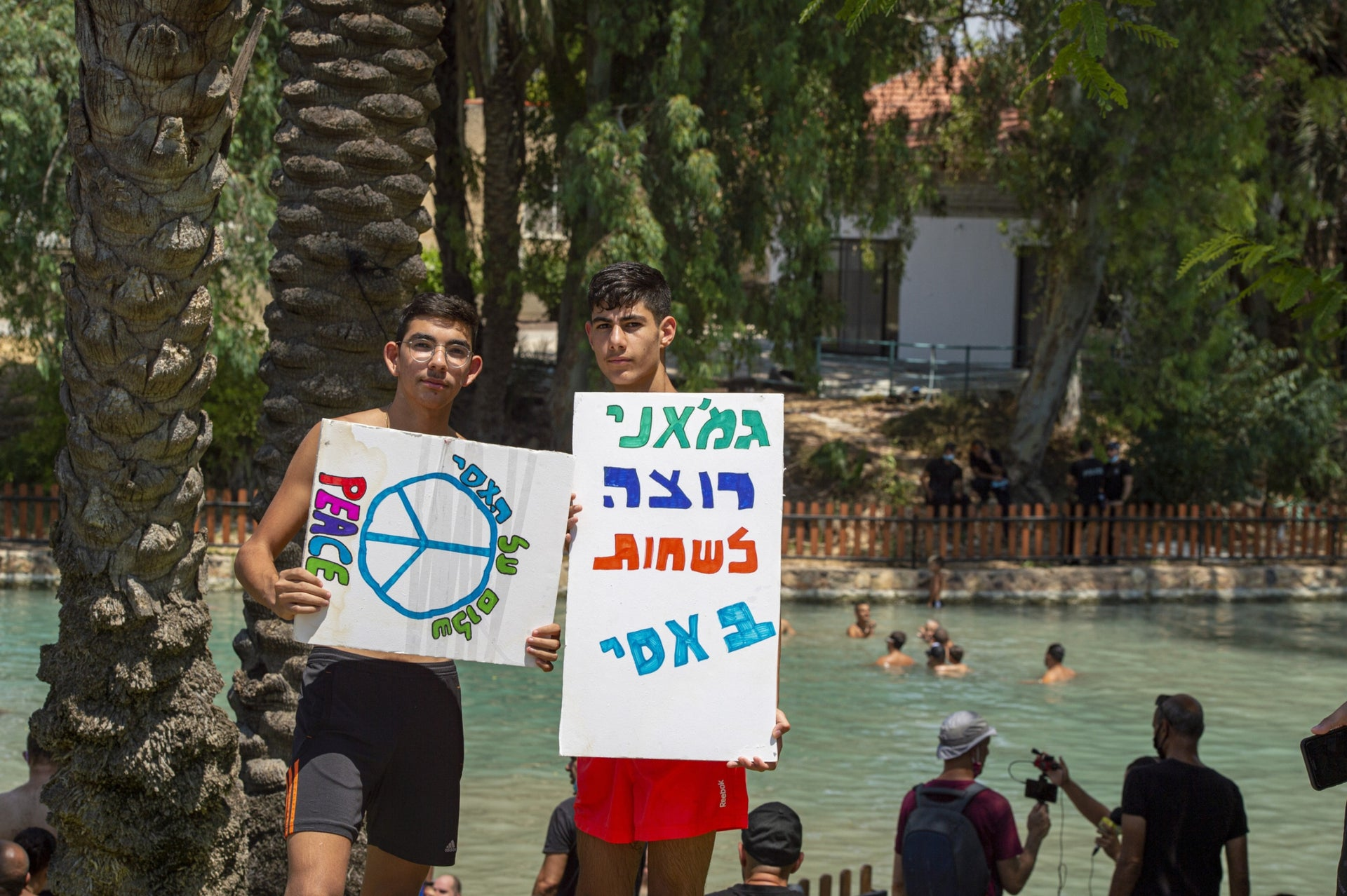 "Protesters on the banks of the Asi in August. The sign on the right says ""I want to swim in the Asi too."""