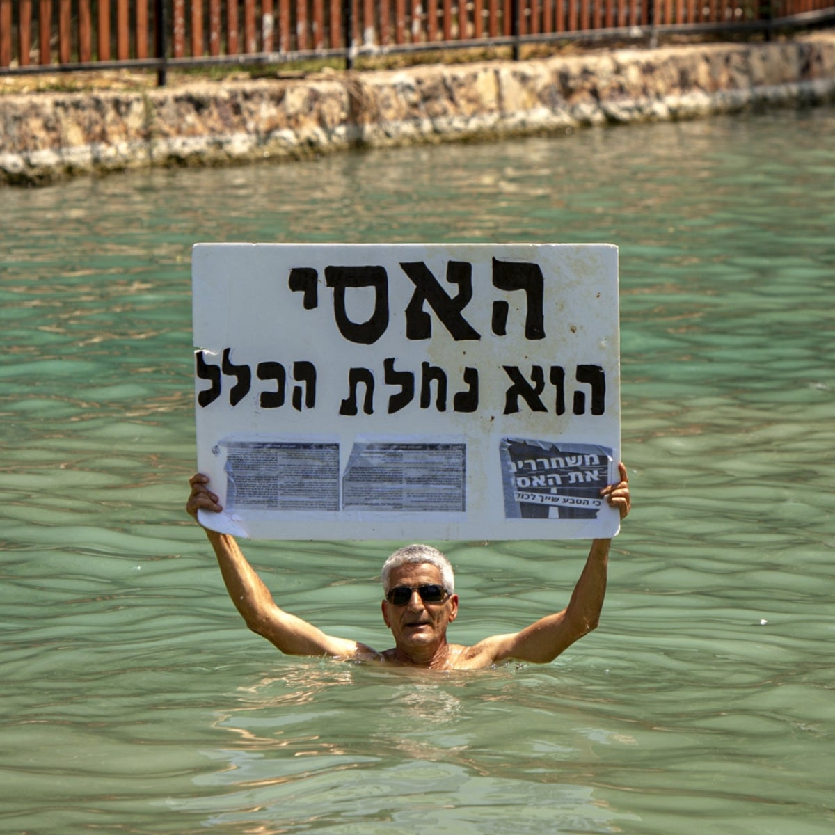 A protester in the Asi stream with a placard stating that it belongs to the public.