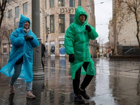 Two people walking through Jerusalem on a rainy winter's day.