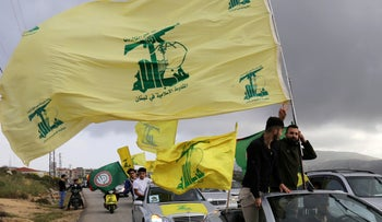A supporter of Lebanon's Hezbollah gestures as he holds a Hezbollah flag in Marjayoun, Lebanon May 7, 2018.