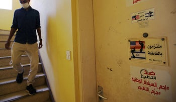 "A building supervisor walks down past the door of ""The Bahraini Society Against Normalization With Zionist Enemy"" in Manama, Bahrain, September 12, 2020."