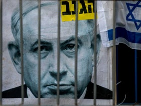 A portrait of Prime Minister Benjamin Netanyahu is seen on a sign at an anti-government protest in Jerusalem, June 27, 2020.