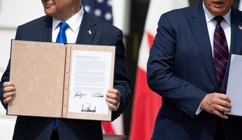 Israeli Prime Minister Benjamin Netanyahu holds up the document after participating in the signing of the Abraham Accords where the countries of Bahrain and the United Arab Emirates recognize Israel, at the White House in Washington, DC, September 15, 2020.
