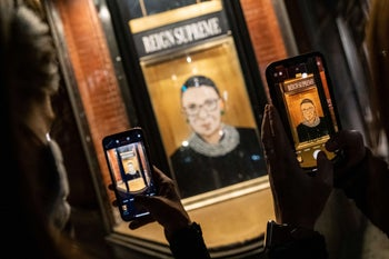 People taking a picture of a portrait of Supreme Court Justice Ruth Bader Ginsburg displayed at a storefront in New York, September 19, 2020.