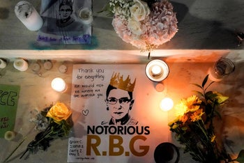 Candles are lit next to pictures of Associate Justice Ruth Bader Ginsburg as people mourn her death at the Supreme Court in Washington, U.S., September 19, 2020.