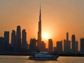 The sun sets behind Burj Khalifa and other high rise buildings, in the Emirati city of Dubai, on September 12, 2020.