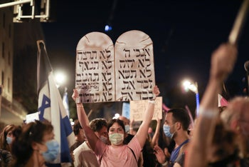 Anti-Netanyahu protester carries a sign with the Ten Commandments, Jerusalem, September 20, 2020.