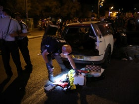 Police search a car after its driver was arrested on suspicion of trying to run over anti-Netanyahu protesters in Jerusalem, September 20, 2020.