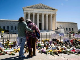 Women embrace at a makeshift memorial for late Supreme Court Justice Ruth Bader Ginsburg on the steps of the United States Supreme Court on September 20, 2020.