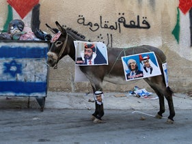 A Palestinian child stands near a donkey with pictures depicting UAE's crown prince and Benjamin Netanyahu during a protest in Kafr Qaddum, the West Bank, September 18, 2020.