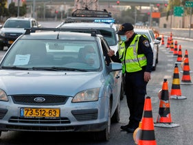 A policeman inspects a driver's papers at a checkpoint in Jerusalem as Israel sees a second nationwide lockdown, September 19, 2020.