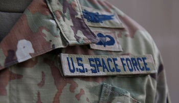 In this photo released by the U.S. Air Force, Capt. Ryan Vickers stands for a photo to display his new service tapes after taking his oath of office to transfer from the U.S. Air Force to the U.S. Space Force at Al-Udeid Air Base, Qatar, Tuesday, Sept. 1, 2020