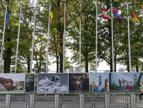 A woman walks past artwork and metal barricades lining the sidewalk outside the United Nations headquarters, New York, September 18, 2020.