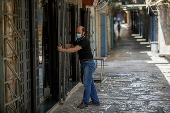 A man closing a shop amid Israel's second nationwide lockdown, in the Old City of Jerusalem, September 21, 2020.
