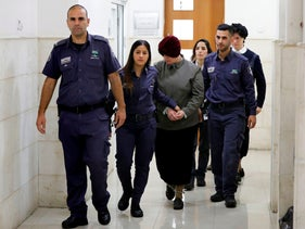 Accused pedophile Malka Leifer is escorted by police as she arrives for a hearing at the District Court in Jerusalem, February 27, 2018.