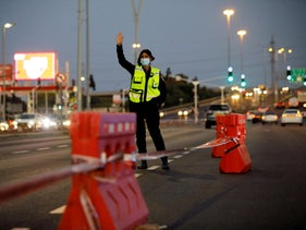 A police officer directs vehicles at a check point during Israel's nationwide lockdown to fight a surge in coronavirus disease infections, in Ashdod, September 21, 2020.
