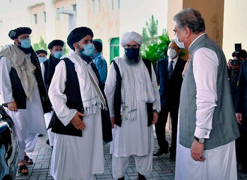 Pakistan's Foreign Minister Shah Mahmood Qureshi, right, greets a Taliban political team on their arrival at the Foreign Ministry for talks. Islamabad, Pakistan, Aug. 25, 2020