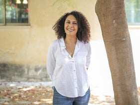 Sheikha Helawy outside her home, standing next to a tree.